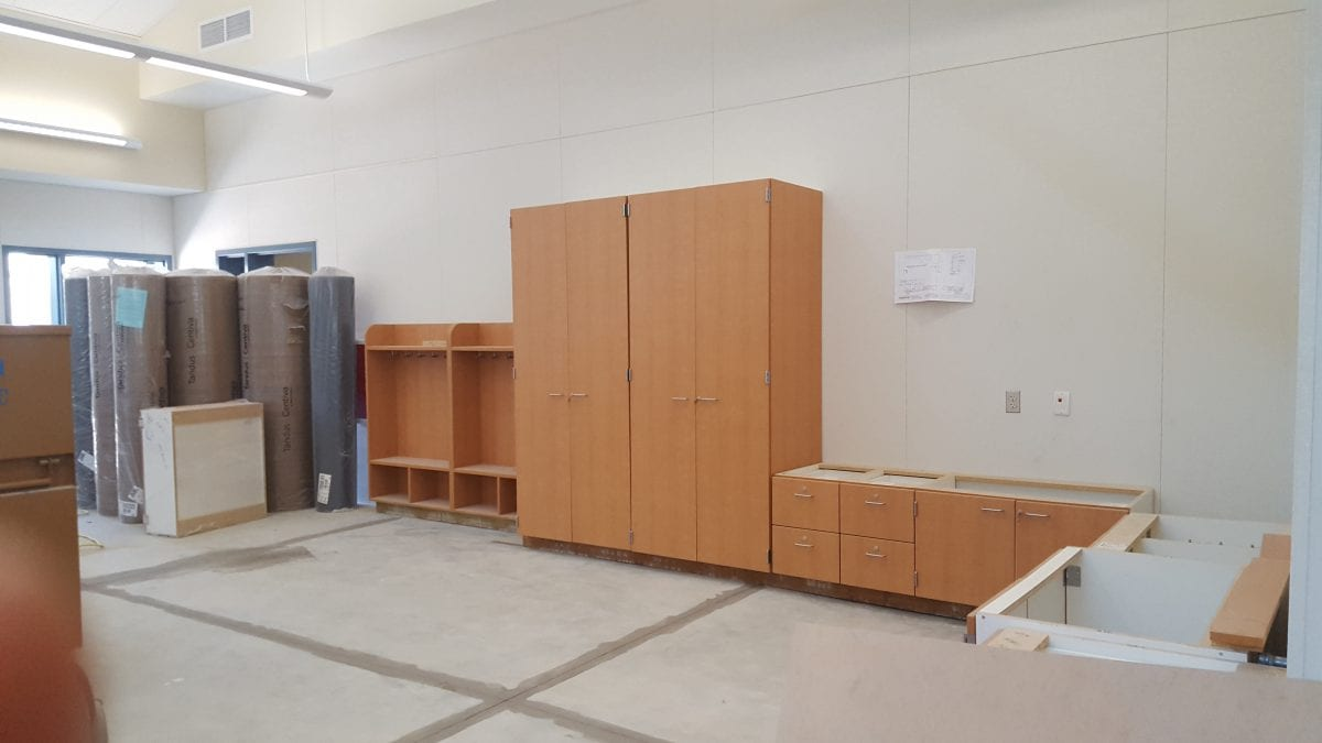 Cabinets, shelves, and rolled up carpeting in a room 8/16