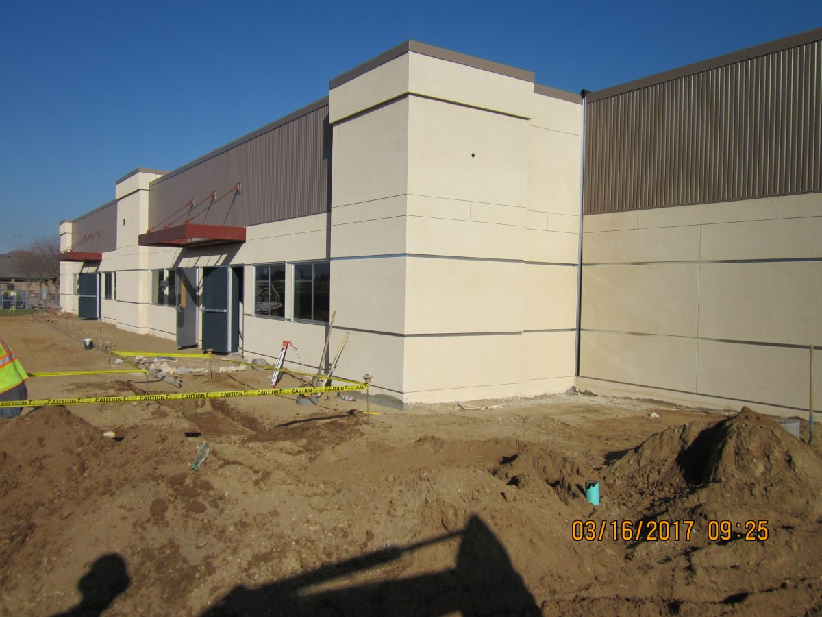 Muddy area outside nearly complete building 3/17