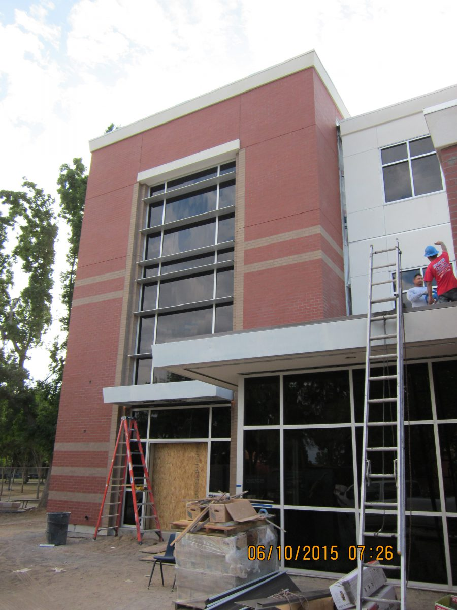 Workers on top of awning of nearly completed building 6/15