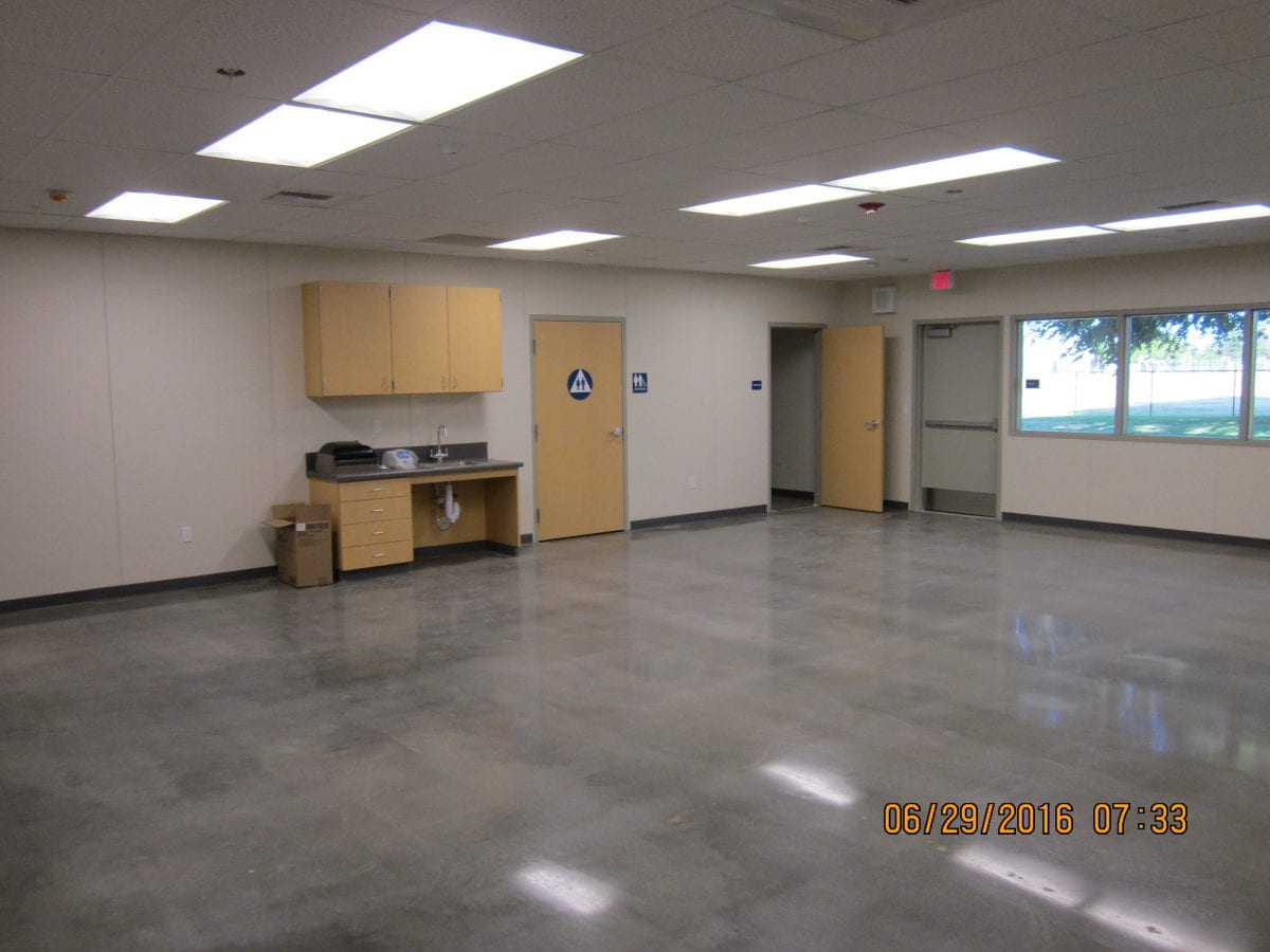 Large empty room with a restroom door and shiny flooring - 6/29/16