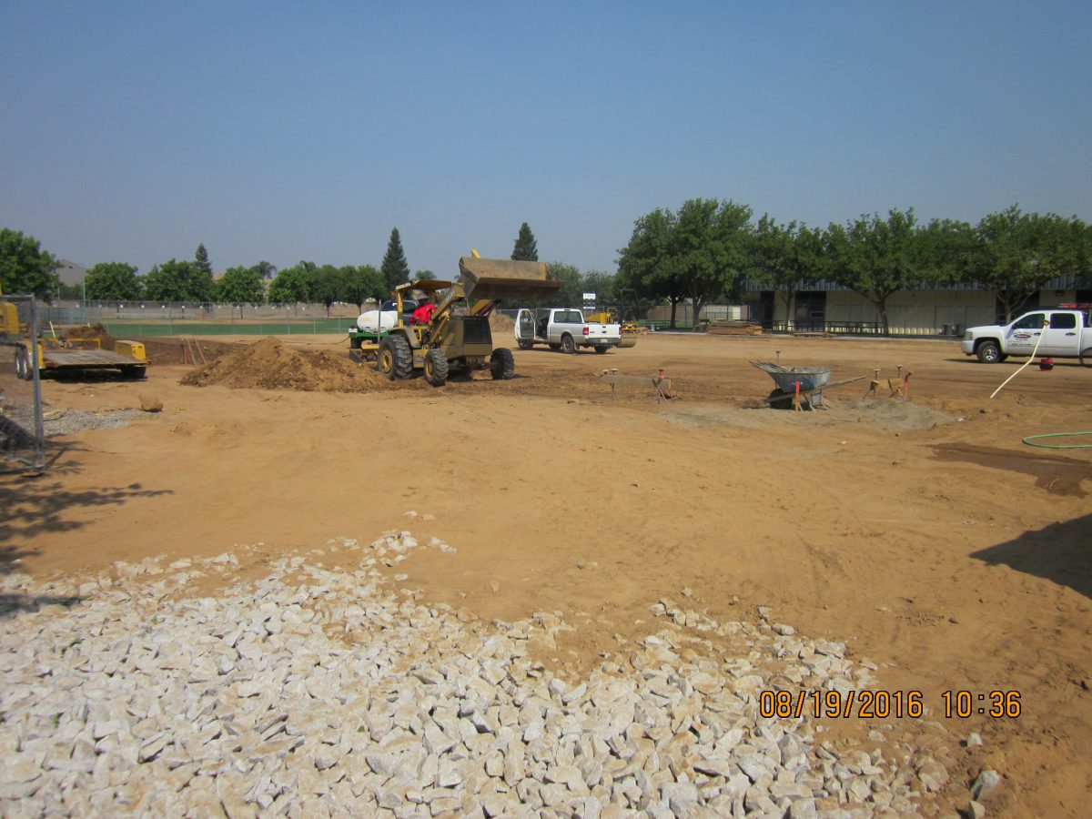 Vehicles in a dirt field with rocks in the corner 8/16