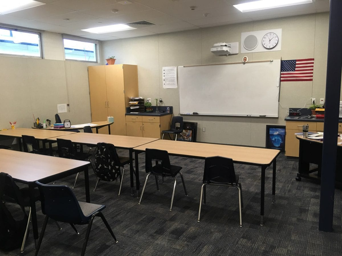 Empty classroom with a whiteboard and a line of desks/chairs