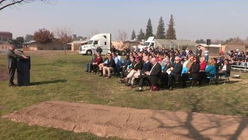 Speaker addressing a group of seated people outside 1/18
