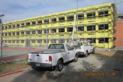 Trucks parked outside yellow walled building under construction 1/15