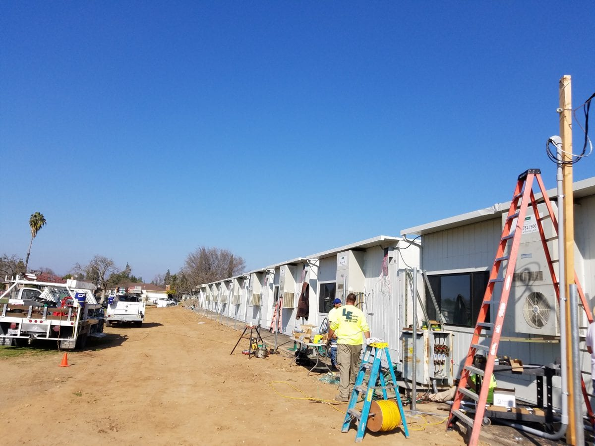Rear view of workers at a line of portable classrooms