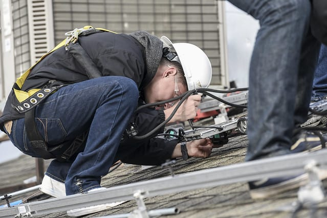 A worker installs a solar panel on a roof.