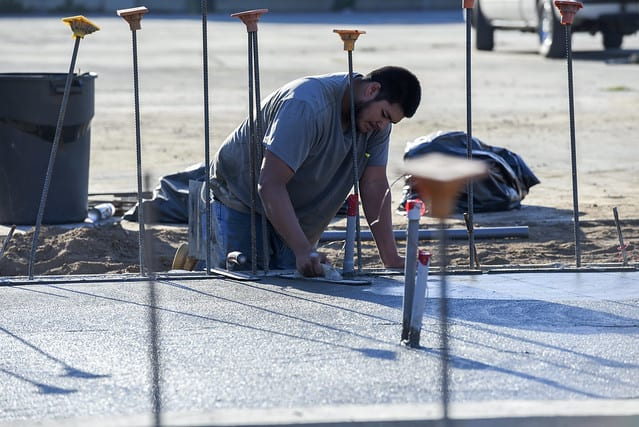 A Fresno Unified worker lays down some concrete.